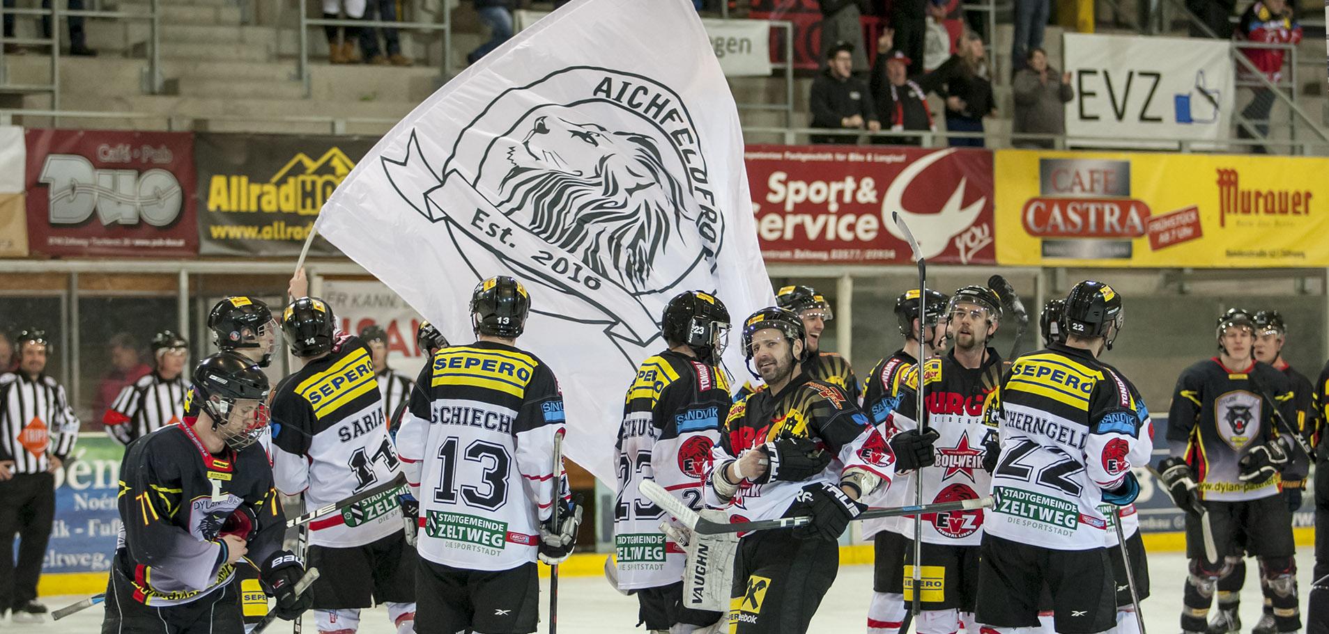 Nach einem dramatischen Spiel feiern die Lions mit der Fahne des Fanclubs